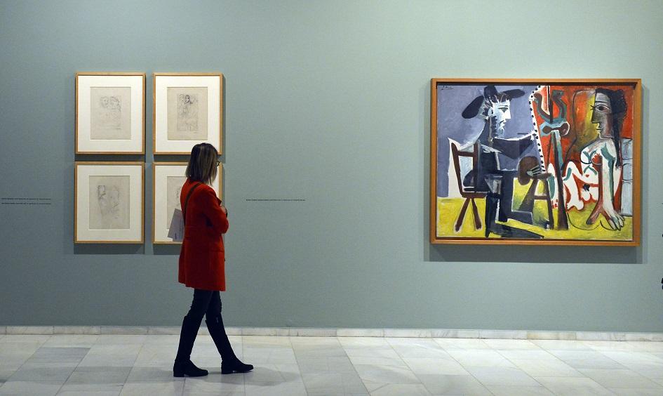 Una visitant contemplant una de les obres clau de l'exposició, l'oli El pintor i la model.