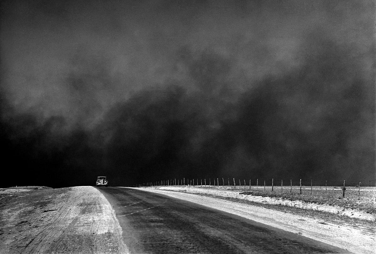 Automòbil circulant per una carretera amb un gran núvols de pols al fons, a Texas              | Arthur Rothstein, 1936