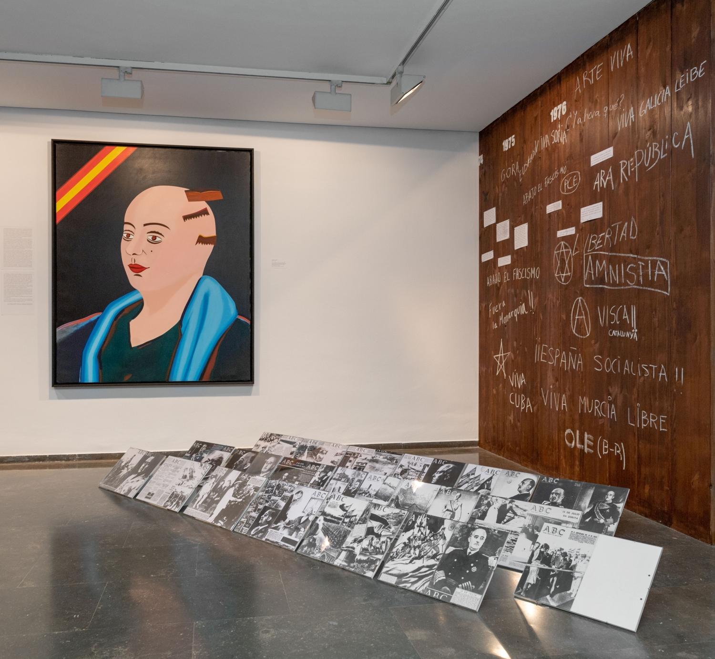 La pintura d'Eduardo Arroyo sobre la dona represaliada, al costat de la instal·lació amb cobertes de l'ABC i la reproducció parcial del panell cronològic de la Biennal del 1976.