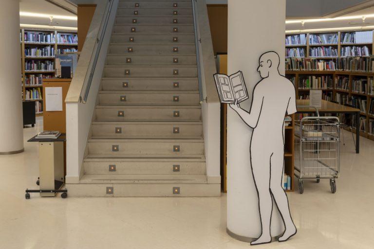 El personatge incomplet, llegint en la biblioteca.