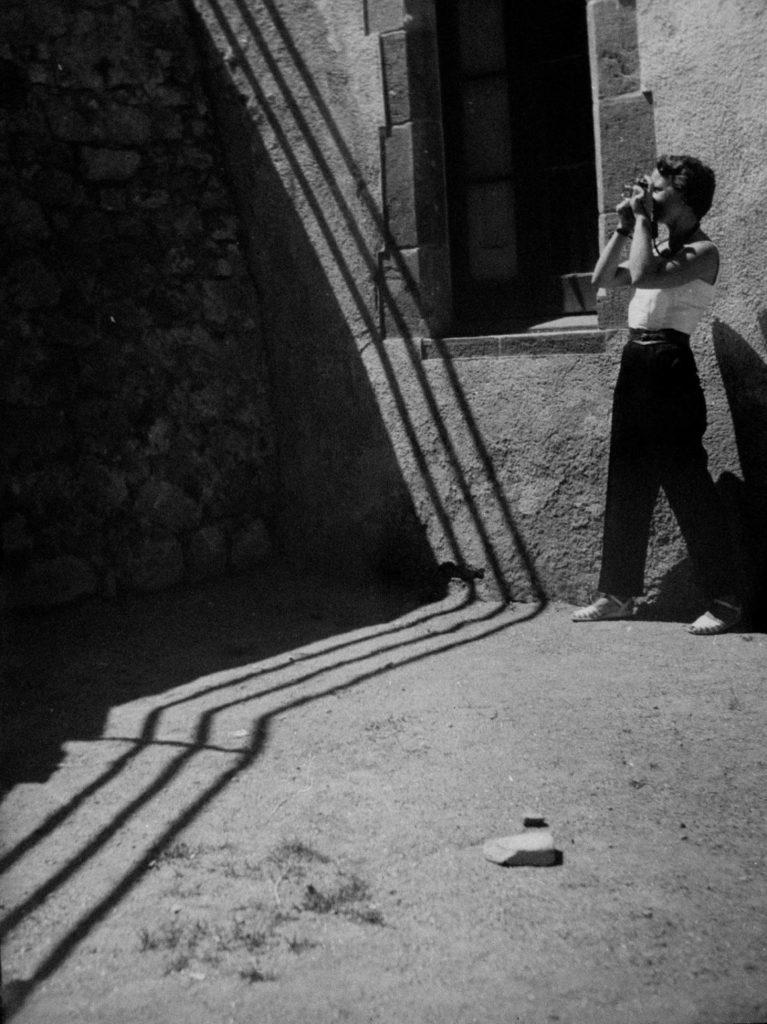 Retrat de Palmira Puig amb la seva càmera, per Marcel Giró, c. 1950.