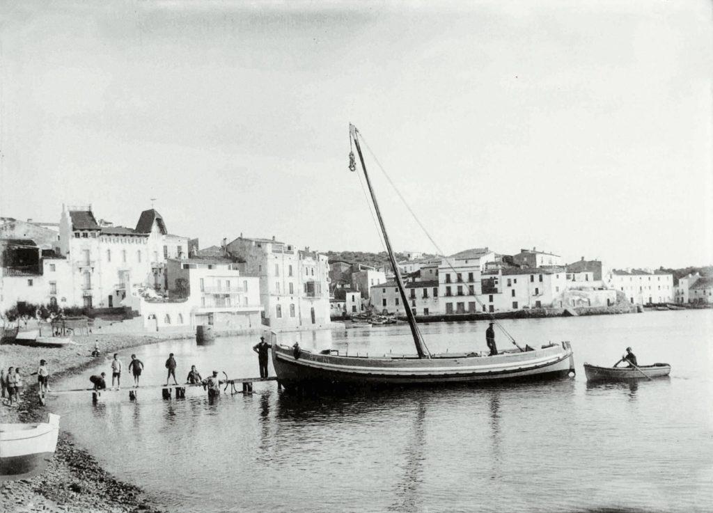 La barca Pedro, adquirida per la família de bussos grecs els Kontos a l'Estartit el 1929, atracada a la Platja Gran de Cadaqués, l'estiu de 1930. Fotografia de placa de vidre: Joan Corney (Arxiu Comarcal Alt Empordà).