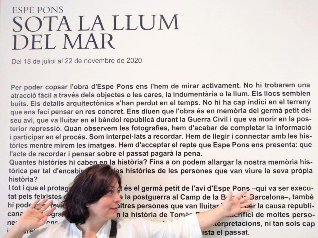Espe Pons davant del text de Cynthia Young, conservadora de l'Arxiu Robert Capa a l'Internacional Center of Photography de NY , i adreçant-se cap al mosaic de fotografies familiars de Tomàs Pons. Fotografia: Jordi Jové.
